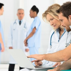 Group Of Doctors Working On Laptop In Hospital